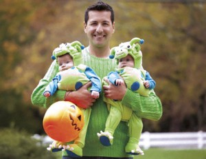 Hispanic father holding twin babies in Halloween costumes