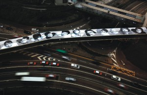 "Vehicles drive past a foot bridge decorated with ""Inside Out"", an artwork by French street artist JR, at Hong Kong's Financial Central District"