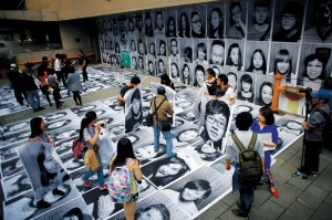 People hold their portraits taken as part of Inside Out art project by French artist JR at Xintiandi area in downtown Shanghai
