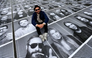 "Artist JR poses with his public art installation ""Actions"" on the Terrace at Somerset House in London"